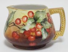 FRENCH LIMOGES PORCELAIN CIDER PITCHER HAND PAINTED WITH CHERRIES. 5 1/4 IN. SOME WEAR TO GOLD ON RIM.