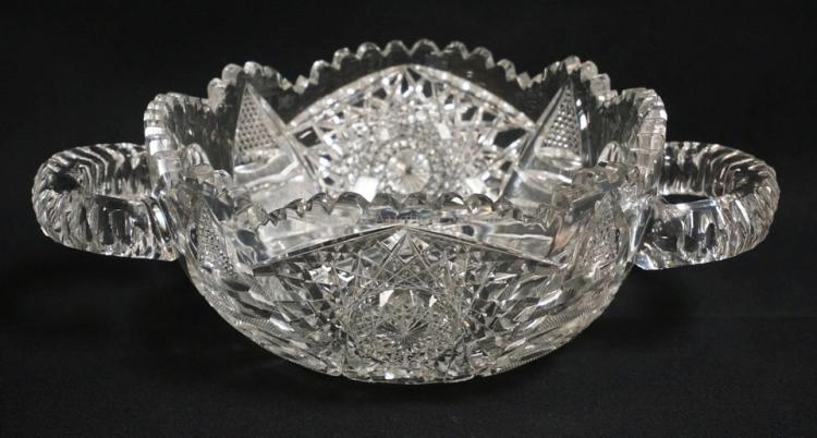 UNUSUAL AMERICAN BRILLIANT PERIOD CUT GLASS BOWL WITH HORIZONTAL APPLIED HANDLES AND VERY INTRICATE CUTTING INCLUDING HOBSTARS AND FANS ALONG WITH INCREDIBLY TINY CANE AND DIAMONDS. ONE CHIPPED TOOTH. 8 INCH DIA. 11 5/8 INCHES ACROSS THE HANDLES. 4 INCHES HIGH.