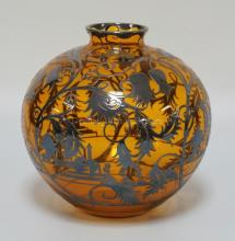 AMBER GLASS BALL VASE WITH STERLING SILVER OVERLAY DEPICTING PAGODAS, LEAVES, AND FLOWERS. POLISHED PONTIL BASE. 8 3/8 INCHES HIGH. 8 3/4 INCHES WIDE.