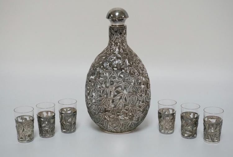 STERLING SILVER OVERLAY DECANTER WITH 6 CORDIALS. ALL PIECES DECORATED WITH BAMBOO SHOOTS AND LEAVES IN .950 SILVER. THE BOTTLE HAS 3 PINCHED SIDES, THE ORIGINAL STOPPER, AND MEASURES 9 1/4 INCHES HIGH.