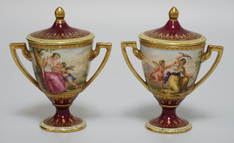 PAIR OF ROYAL VIENNA DIMINUTIVE LIDDED URNS. ARTISTS SIGNED *C. WEH*. VIENNA BEEHIVE MARK ON THE BOTTOM ALONG WITH THE SCENE TITLES OF *RINALDO UND ALMIDA, VENUS UND AMOR, AMORE ENTWAFFNET, AND DESEUS FINDETDAS, SCHWERT SEINES VATERS*. 4 5/8 INCHES HIGH. HAS A FEW MISSING ENAMELED JEWELS.