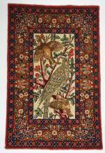 FINELY WOVEN HAND KNOTTED PERSIAN RUG WITH A FLOWERING TREE AND BIRDS IN THE CENTER WITH A FLORAL BORDER. 18 1/2 X 28 1/2 INCHES.