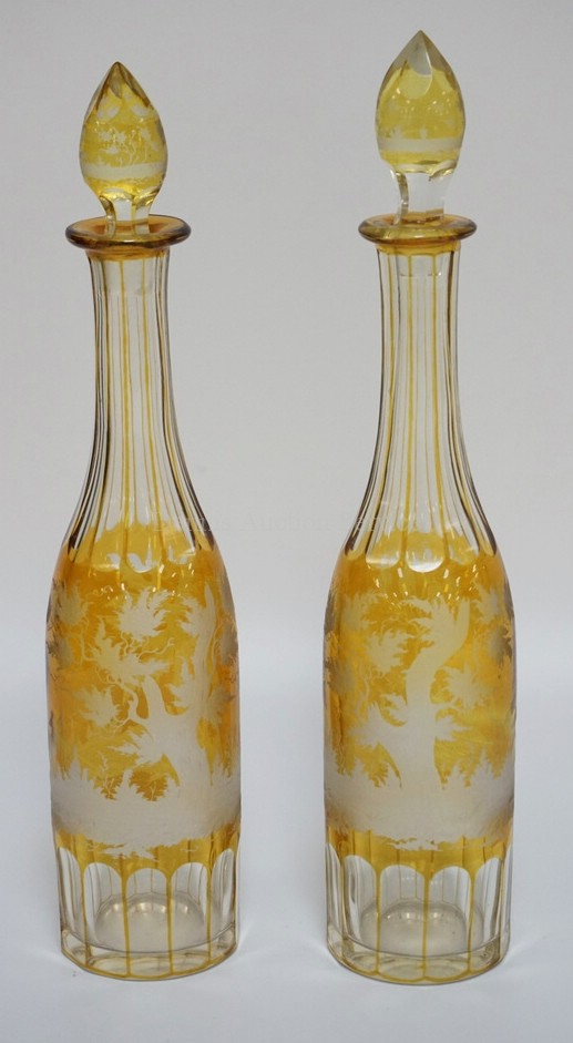 PAIR OF AMBER STAINED CUT TO CLEAR DECANTERS WITH ORIGINAL STOPPERS. PANEL CUT BASES AND NECKS WITH WHEEL CUT DESIGNS OF DEER WITH TREES. TALLEST IS 15 INCHES.