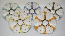 LOT OF 5 MATCHING PORCELAIN OYSTER PLATES IN VARIOUS COLORS. EACH WITH 6 WELLS. 9 1/2 INCH DIA.