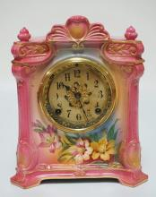 ROYAL BONN PORCELAIN CLOCK WITH AN ANSONIA MOVEMENT. PINK CASE DECORATED WITH FLOWERS. COMES WITH PENDULUM AND KEY. BACK COVER MISSING AND THERE IS A SHORT HAIRLINE ON THE BACK AT THE LEFT SCREW HOLE. 11 5/8 INCHES HIGH. 9 3/4 INCHES WIDE.