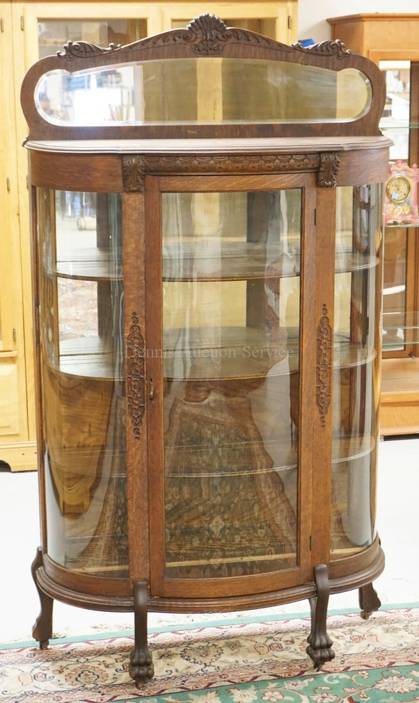 ANTIQUE CARVED OAK CHINA CABINET WITH A BOWED GLASS DOOR AND SIDES. PARTIAL MIRRORED BACK WITH A MIRRORED CREST. CARVED PAW FEET. 75 1/2 INCHES HIGH. 44 INCHES WIDE.