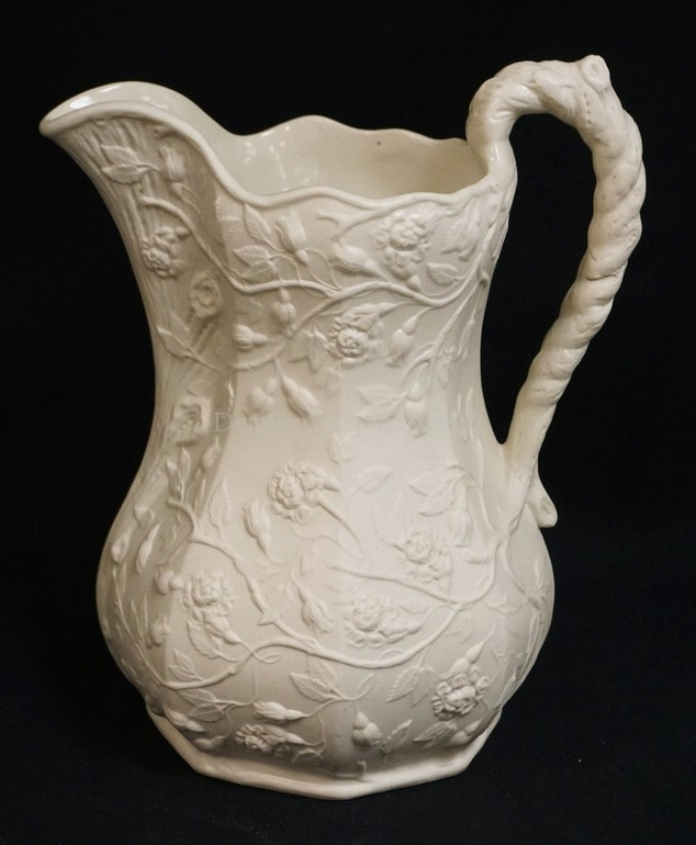 ANTIQUE PARIAN PITCHER RELIEF DECORATED WITH BRANCHES OF LEAVES AND FLOWERS. 10 INCHES HIGH.