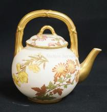 ANTIQUE ROYAL WORCESTER INDIVIDUAL TEAPOT DECORATED WITH HAND PAINTED FLOWERS AND GOLD ENCRUSTED SPOUT AND HANDLE. 6 1/2 INCHES HIGH.