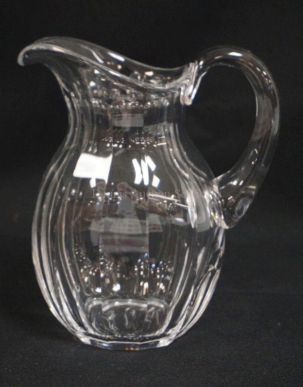 HEAVY AND HIGH QUALITY CRYSTAL PITCHER WITH AN APPLIED HANDLE AND A PANELED BODY. UNSIGNED. 8 1/4 INCHES HIGH.