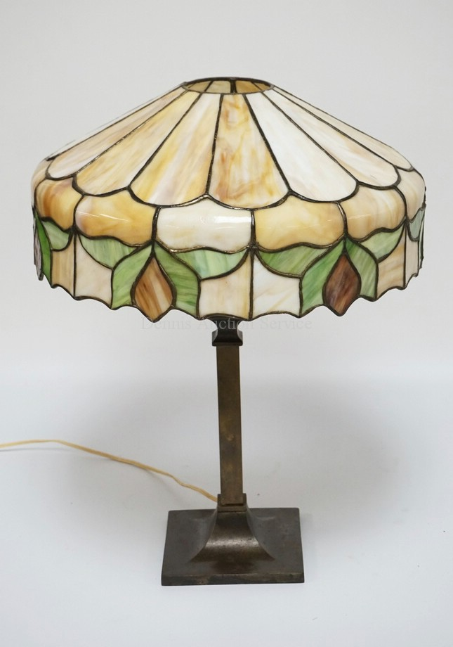 ANTIQUE TABLE LAMP WITH A CARAMEL AND GREEN SLAG SHADE ON AN IRON BASE WITH A BRONZED FINISH. 21 1/2 INCHES HIGH. A FEW OF THE SMALL PANELS HAVE CRACKS.