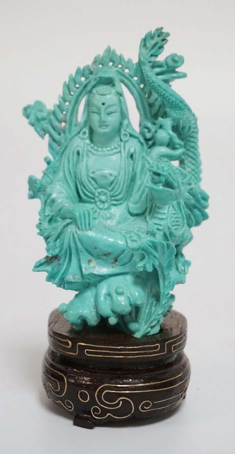 CARVED CHINESE TURQUOISE FIGURE OF GUANYIN WITH A DRAGON. HAS INCLUIONS. WOODEN BASE WITH BRASS INLAY. 3 5/8 INCHES HIGH.