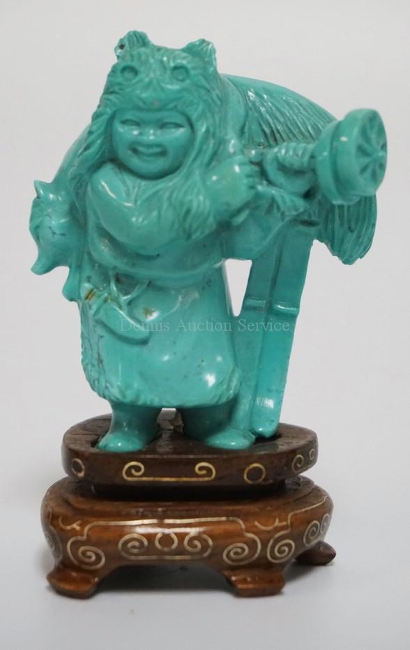 CARVED CHINESE TURQUOISE FIGURE OF A MAN WEARING A PELT AND CARRYING A KITSUNE. HAS INCLUIONS. WOODEN BASE WITH BRASS INLAY. 2 1/4 INCHES HIGH.