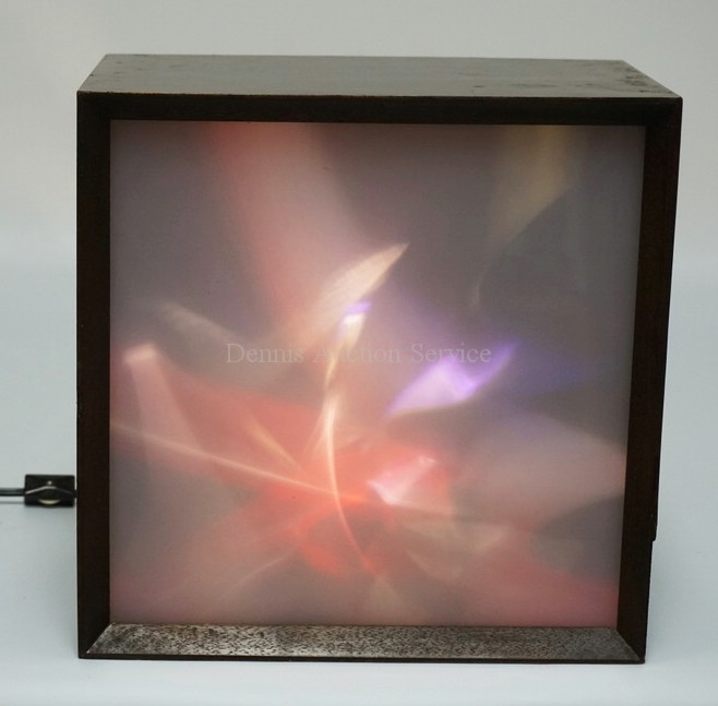 MID CENTURY MODERN LIGHT BOX. *LUMIA* BY LIGHTOLIER. FRONT PANEL LIGHTS UP WITH PRISM LIKE COLORS THAT SLOWLY MOVE AND TWIST AROUND. 11 1/2 INCHES SQUARE. HAS A PIECE OF VENEER MISSING ON THE RIGHT SIDE.