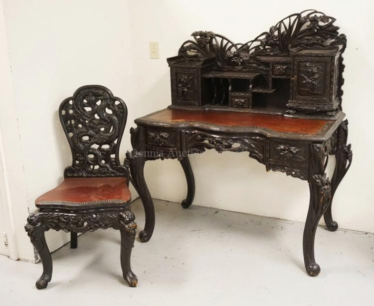 INTRICATELY CARVED ASIAN DESK AND CHAIR. DEEP RELIEF CARVINGS OF FLOWERS WITH STIPPLED BACKGROUNDS. 48 INCHES WIDE. 54 1/4 INCHES HIGH.