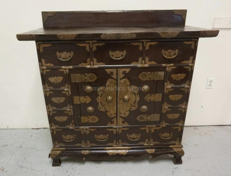 ASIAN CABINET WITH 7 DRAWERS AND 2 DOORS. BOUND WITH DECORATIVE BRASS. DOVETAILED CONSTRUCTION. 48 INCHES WIDE. 47 1/4 INCHES HIGH.
