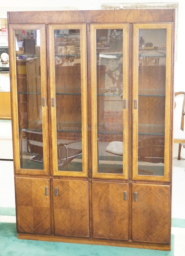 MODERN WALNUT CHINA CABINET WITH A LIGHTED INTERIOR AND GLASS SHLEVES. 4 DOOR CABINET BELOW. 54 INCHES WIDE. 80 INCHES HIGH.