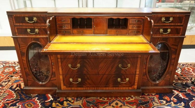 BANDED MAHOGANY SIDEBOARD WITH THE TOP DRAWER BEING A DROP FRONT DESK WITH A COMPARTMENTED INTERIOR. TRIPTYCH LEATHER TOP. OVAL CONVEX GLASS PANELS IN THE DOORS. 65 3/4 INCHES WIDE. 36 INCHES HIGH.
