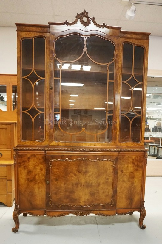 CHINA CABINET WITH FIGURED VENEER AND CARVED ACCENTS. 79 1/2 INCHES HIGH. 49 1/2 INCHES WIDE.