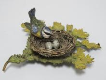 COLD PAINTED BRONZE FIGURE OF A BIRD IN A NEST WITH 2 EGGS. HAS A LOOSE REPAIR TO THE STEM OF THE BRANCH. 5 3/4 INCHES LONG. 2 3/8 INCHES HIGH.