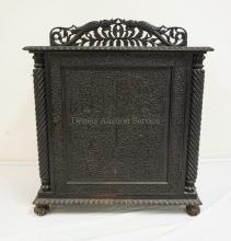 INTRICATELY CARVED ONE DOOR CABINET WITH AN OPENWORK BACKSPLASH. 36 INCHES WIDE. 43 INCHES HIGH. 20 1/2 INCHES DEEP.