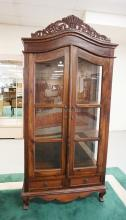 WALNUT CURIO CABINET WITH SOME CARVED DECORATION. ONE GLASS DOOR HAS A CRACK. 82 3/4 INCHES HIGH. 40 INCHES WIDE.