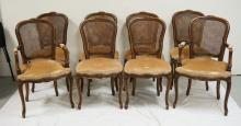 SET OF 8 DINING CHAIRS WITH FRENCH STYLE CARVED WALNUT FRAMES AND CANED BACKS. 37 1/2 INCHES HIGH.