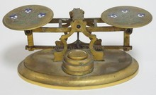 UNUSUAL SMALL BRASS BALANCE SCALE W/ENGRAVED AND ENAMELLED WEIGHING SURFACES 7 3/4 IN WIDE. COMES W/ 3 BRASS WEIGHTS.