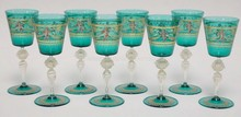 SET OF 8 TEAL AND CRYSTAL HAND PAINTED VENETIAN GLASS GOBLETS. CLEAR STEMS HAVE 2 BLOWN AND RIBBED SECTIONS W/ GOLD FLECKS AND APPLIED PRUNTS. TOPS ARE HAND PAINTED W/ CHERUBS AND LION HEADS. FOLDED FOOT RIMS. 7 3/8 IN H
