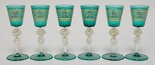 SET OF 6 TEAL AND CRYSTAL HAND PAINTED VENETIAN GLASS WINES. CLEAR STEMS HAVE 2 BLOWN AND RIBBED SECTIONS W/ GOLD FLECKS AND APPLIED PRUNTS. TOPS ARE HAND PAINTED W/ CHERUBS AND LION HEADS. FOLDED FOOT RIMS. 5 3/8 IN H