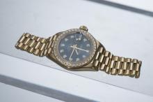 Montre bracelet Rolex Oyster perpetual en or jaune .750 avec couronne de diamants, index diamants et cadran en or bleu et guichet de date à 3h.