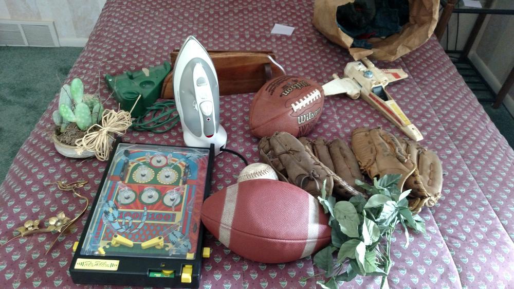 toy pin ball game, ball glove, iron, broken X-wing fighter (star wars), shelf, misc