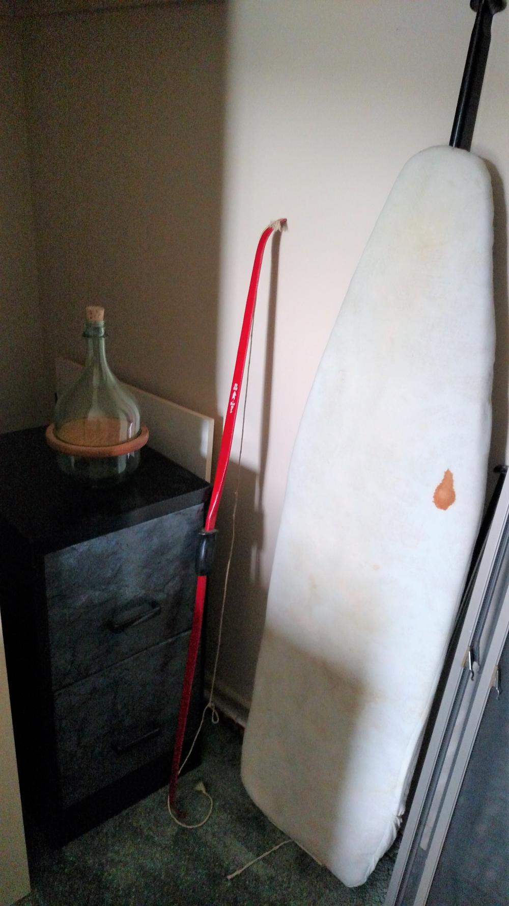 iron board, 2 drawer file cabinet, games, bottle, bow, misc