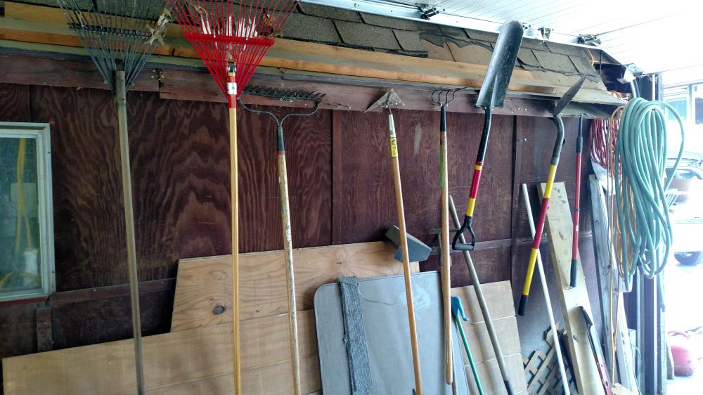 side wall contents - rakes, garden tools, wood, pitch forks, ext. cords