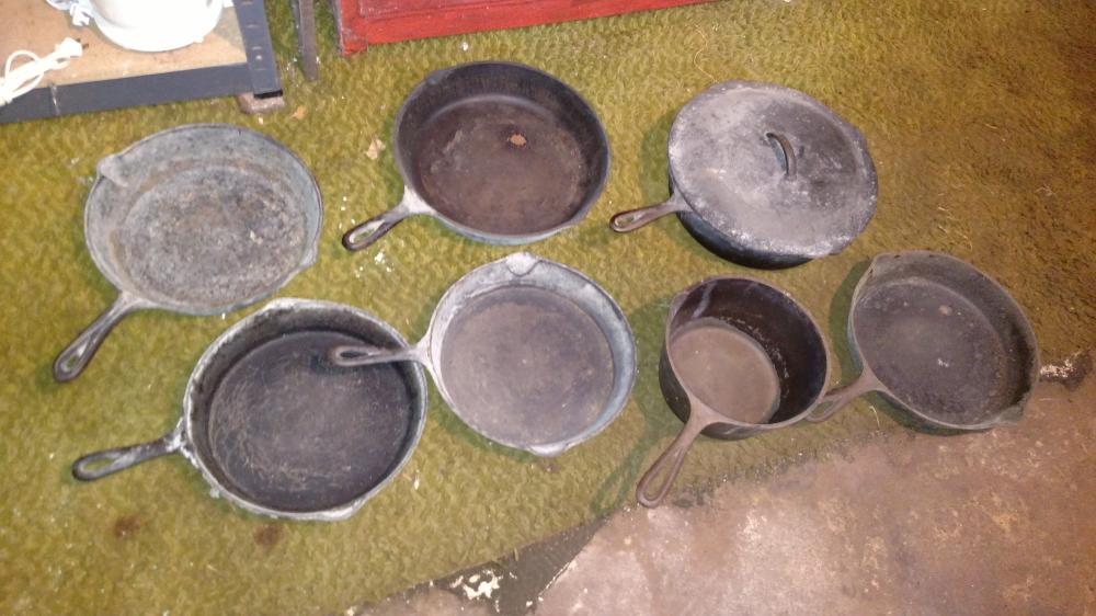 7 unmarked iron skillets and pans