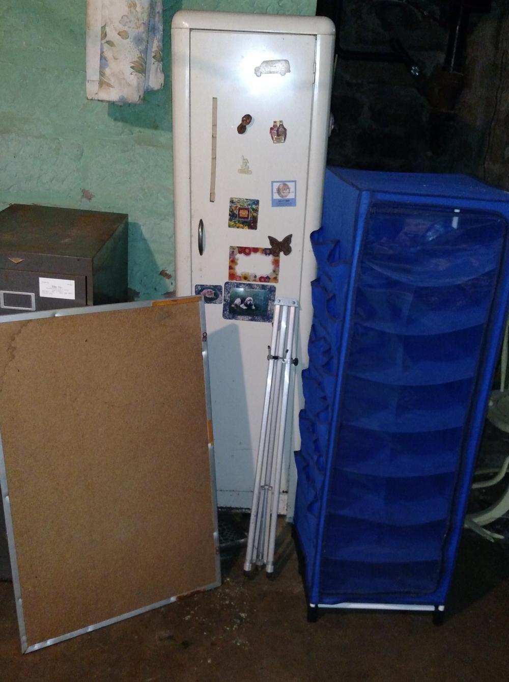 white metal 1 door cabinet, canvas shoe rack, cork board and easle