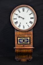 Horloge à suspendre en bois richement marqueté, vitre peinte sous verre en bleu et doré. Cadran...