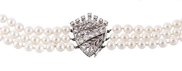 A three strand diamond necklace with a diamond set