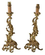 A pair of Continental gilt metal table lamps modelled as figural candelabra...