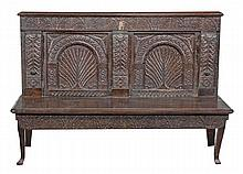 A carved oak settle with crewel work cushion, 17th