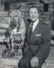 Disney, Walt - Black and white, three quarter photograph of Walt Disney seated...