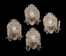 A set of four silver plated metal twin light wall appliques in early 18th...