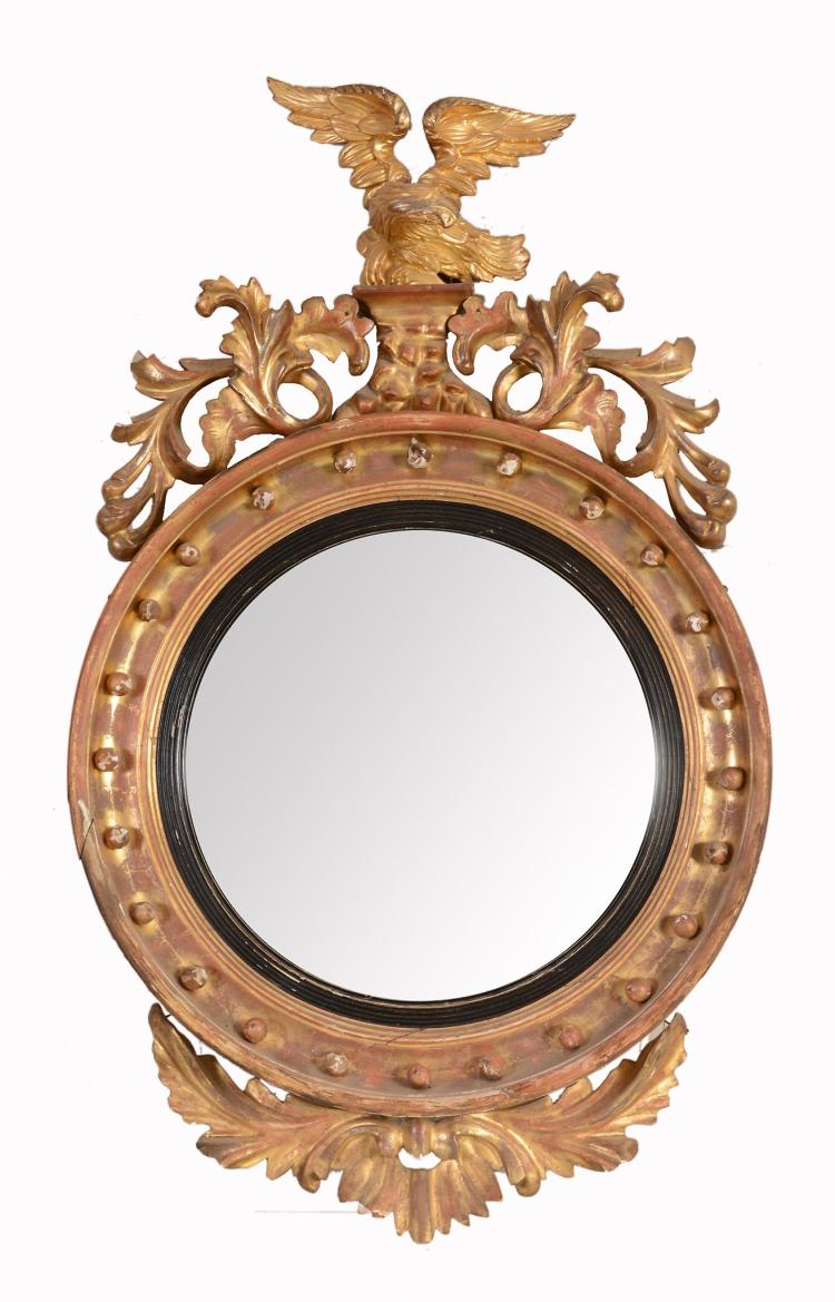 A Regency giltwood convex wall mirror, circa 1815, with associated eagle