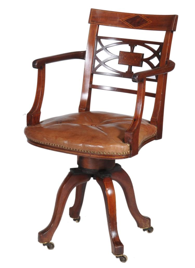 A mahogany and buttoned leather upholstered revolving desk or library armchair