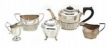 A silver matched three piece oval tea service by William Aitken