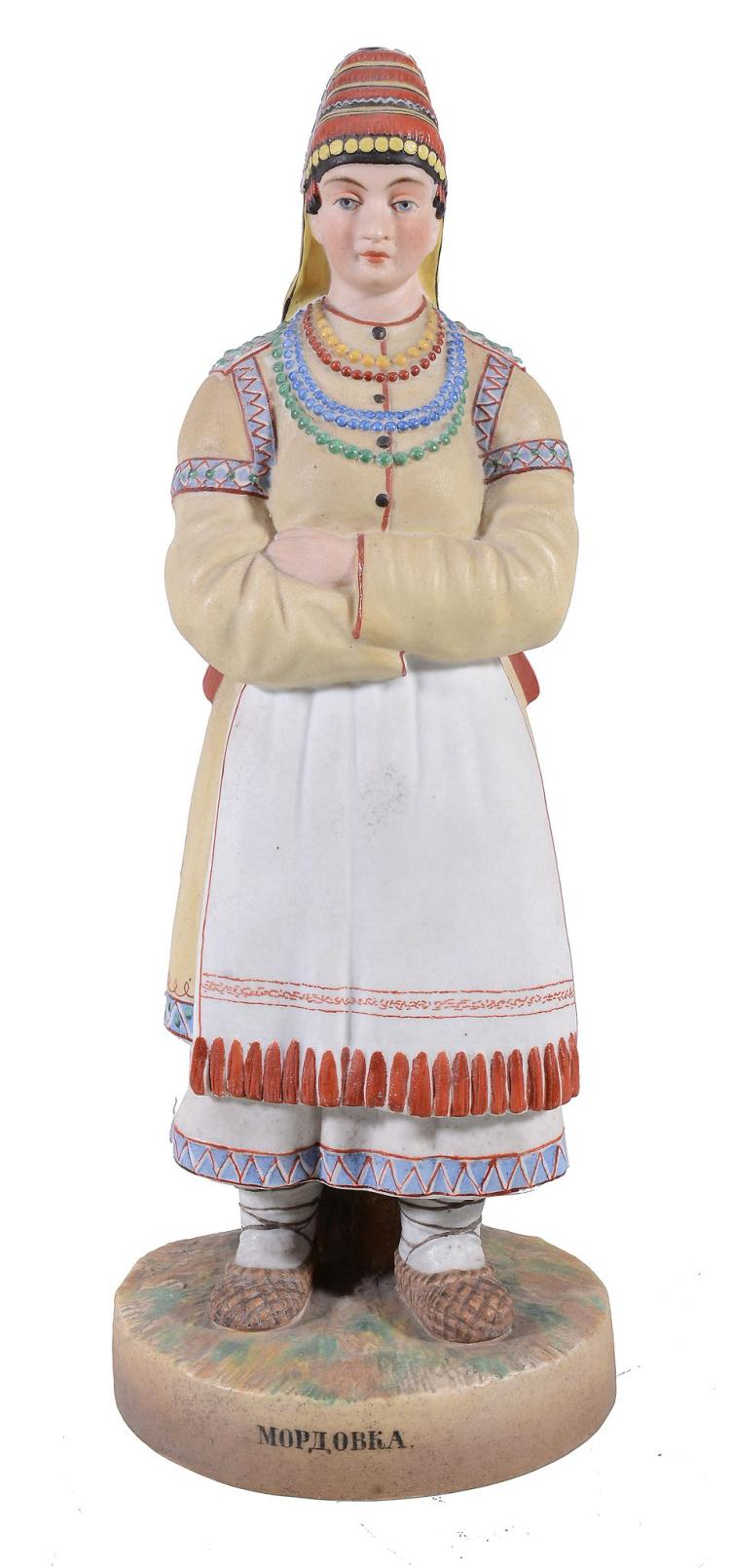 A Moscow biscuit porcelain figure of a woman in peasant dress