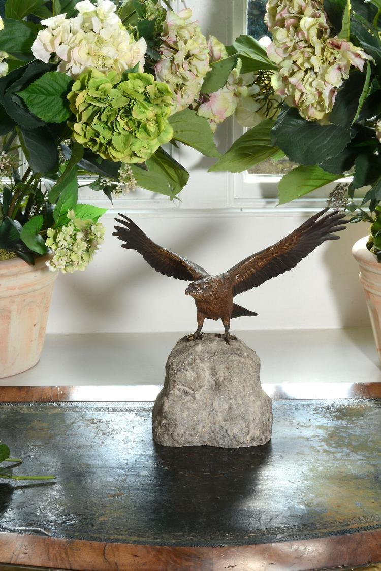 A Viennese cold painted bronze and granite mounted model of an alighting eagle
