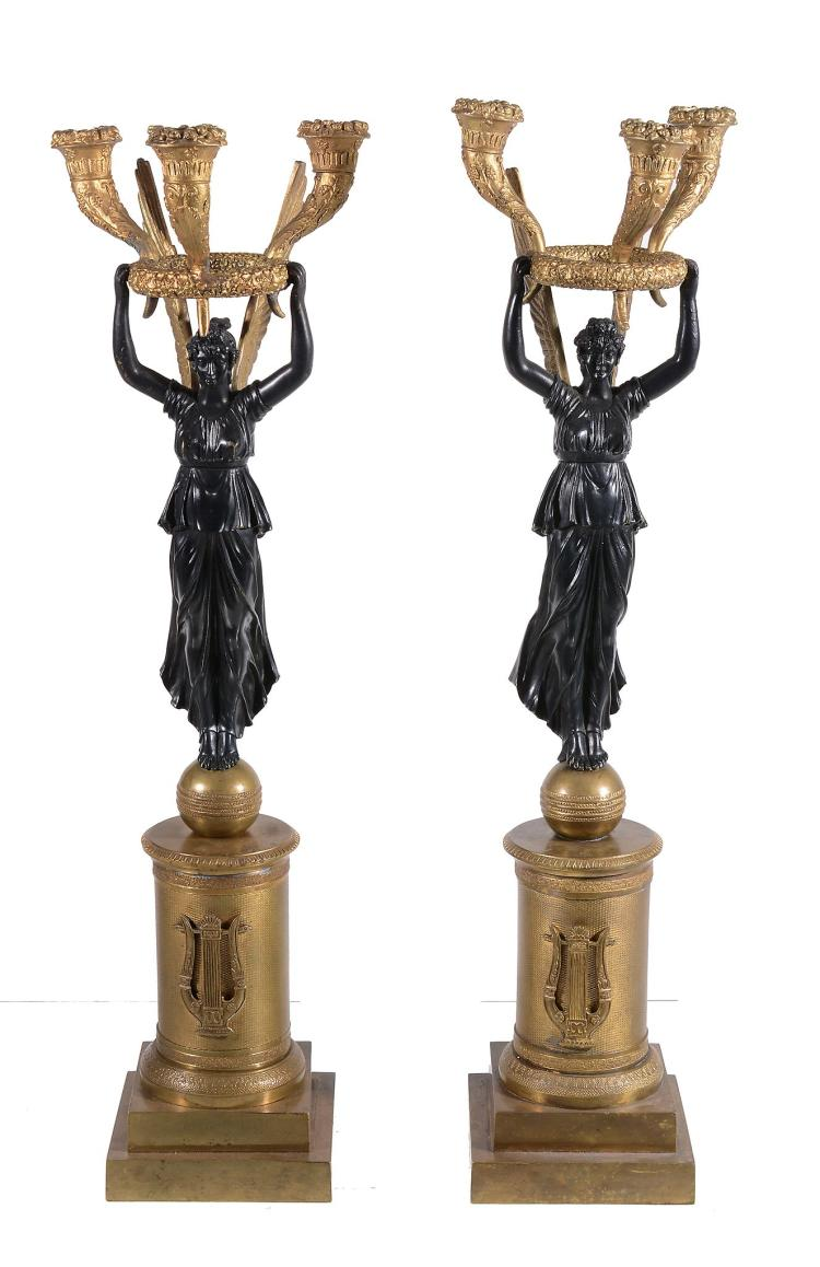 A pair of Empire gilt and patinated bronze three light figural candelabra
