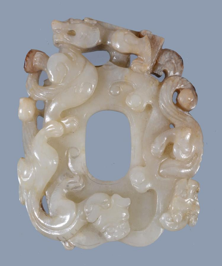 A Chinese celadon jade dragon pendant, with small russet and black inclusions