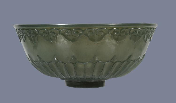 A Chinese Mughal-style green jade bowl, the exterior carved with a band of...