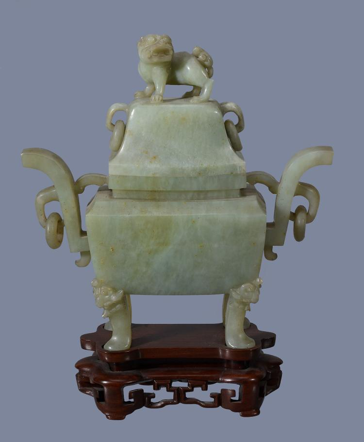 A Chinese celadon jade two-handled vase and cover, supported on four feet